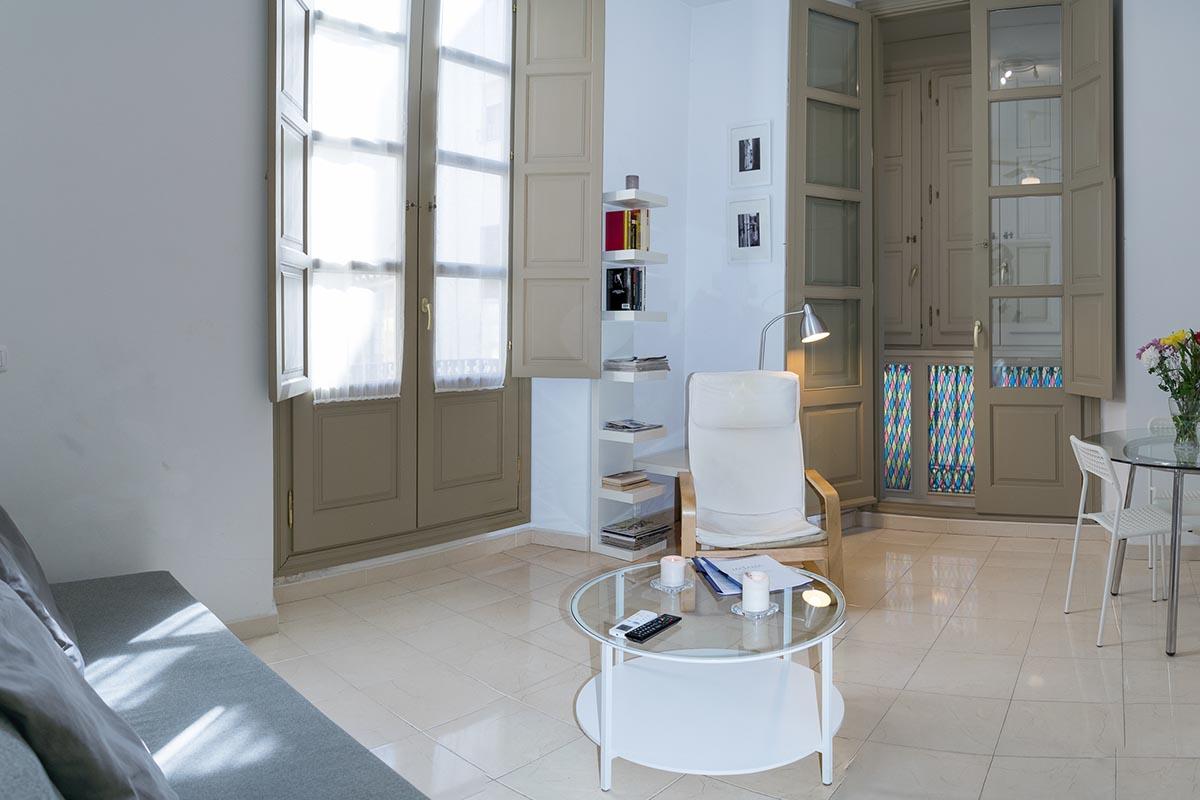 Vista de la mesa y ventanas en el salón del apartamento turístico MALAMA B2 en el centro de Málaga